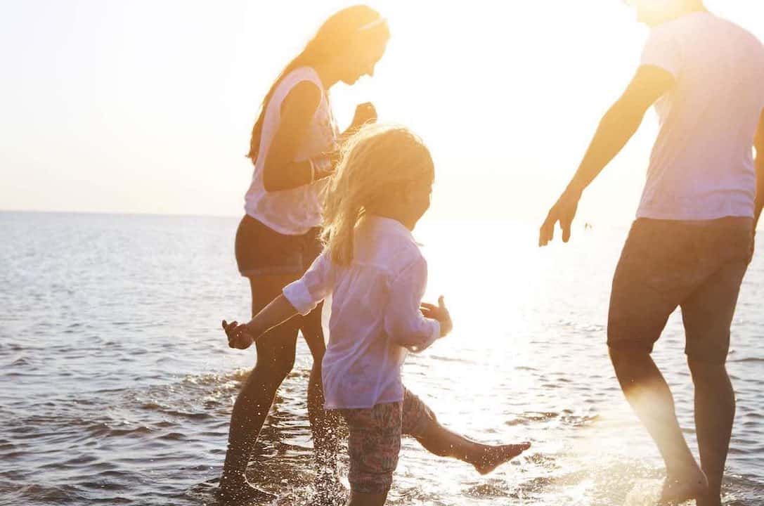happy young family having fun running on beach splashing in water at sunset